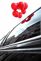 Red balloons on a limousine