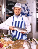 Fishmonger at work, holding Sea brass, portrait