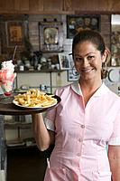 Smiling waitress with french fries and sundae