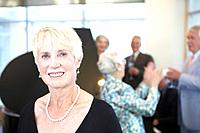 Portrait of senior woman, friends dancing in background by piano