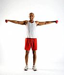 Young man using dumbbells with arms outstretched, studio shot