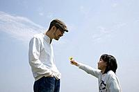 Girl 7_9 giving flower to father, side view