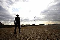 Businessman in field with wind turbine