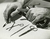 Man arranging surgical tools, close up of hands