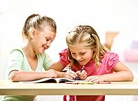 Two girls playing with crayons and coloring books