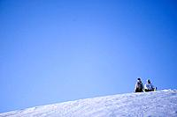 Young couple sitting near slope on snowcoverd mountain, Kuehtai, Tyrol, Austria