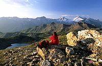 Hiker resting at Pluderlingsattel with view to lake Junsee, Gefrorene Wandspitzen and Olperer, Tuxer range, Tyrol, Austria