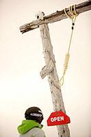 Skier standing next to symbolic gallows for poachers, Castle Mountain ski resort, Southern Alberta, Canada