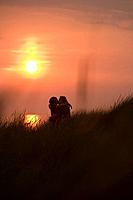 Sunset Silhouette of Romantic Couple in Dunes at Henne Strand Beach, Henne Strand, Central Jutland, Denmark