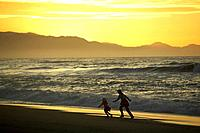 Mother with child, sunset, beach near Haast, Westcoast, South Island, New Zealand