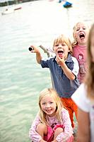 Children playing on the jetty, pulling faces, Woerthsee, Upper Bavaria, Bavaria, Germany