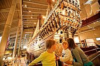 Mother and two children looking at a Vasa Schiff in the Vasa museum, Stockholm, Sweden