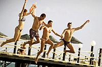 Young people jumping from jetty