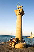 People resting on base of column with deer Elafos at port entrance of Mandraki harbour translated literally: fold, column with doe Elafia in backgroun...