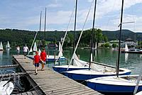 Two boys on landing stage with sailing boats, lake Mattsee, Salzkammergut, Salzburg, Austria