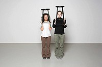 Women holding up stools