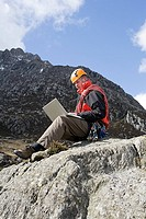 A man using a laptop on a rock