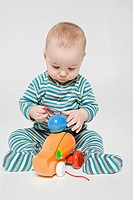 A baby boy playing with a toy duck (thumbnail)