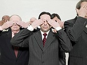 Businessmen covering eyes