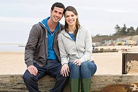 Couple sitting on a fence at the beach