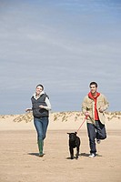 Couple running on beach with dog