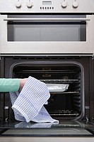 Person putting dish in oven