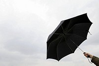 Person holding black umbrella against the rain