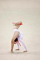 Young woman performing rhythmic gymnastics with clubs