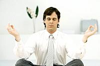 Businessman sitting in lotus position, eyes closed