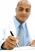 Doctor writing a prescription, focus on hand in the foreground
