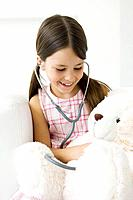 Girl listening to teddy´s bear´s heart with stethoscope