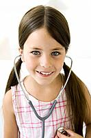Girl listening to her own heart through stethoscope