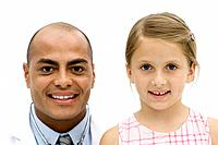 Male doctor beside girl, both smiling at camera, portrait