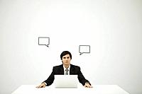 Businessman sitting with laptop computer, blank word bubbles on wall behind him