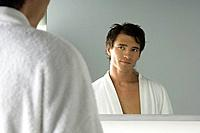 Man in bathrobe smiling at self in mirror