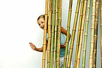 Girl standing behind bamboo, smiling and waving at camera