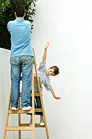 Father and son standing on ladder, boy pretending to be a plane (thumbnail)