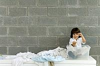 Little boy sitting in plastic storage container, laundry strewn beside him, pretending to drive