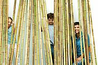 Father and two children peeking through bamboo at camera, all smiling