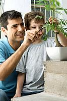 Father and son pruning plant together, smiling (thumbnail)