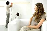Man using drill to attach wood to wall, woman in foreground watching over her shoulder