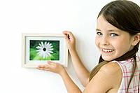Little girl holding framed picture against wall, smiling over shoulder at camera