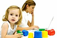 Little girl playing with toys while young woman uses computer in background