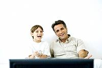 Father and son watching TV together, boy holding remote