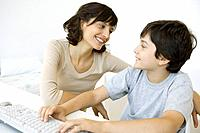 Mother and son sitting and smiling at each other, boy using keyboard