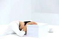 Woman with head down on desk, arm obscuring face, hand on top of stack of paper