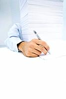 Arm reaching around massive stack of paper to write on a single sheet