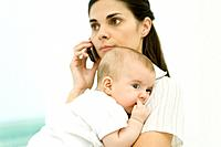 Mother holding infant, using cell phone