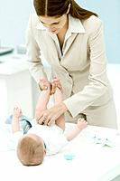 Professional woman changing baby's diaper on desk