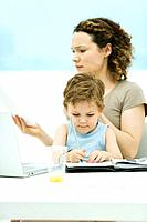 Mother holding son on lap, sitting in front of laptop, frowning at document